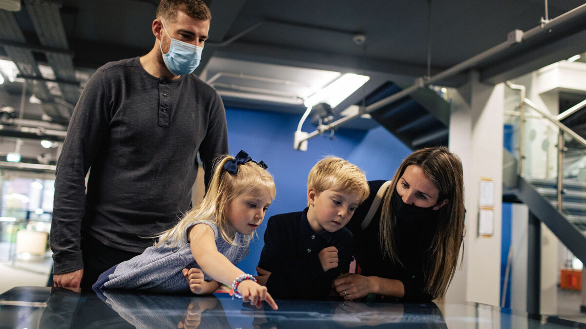 A family is learning anatomy using Inside Explorer installed on a multi touch table at The Aberdeen Science Centre.