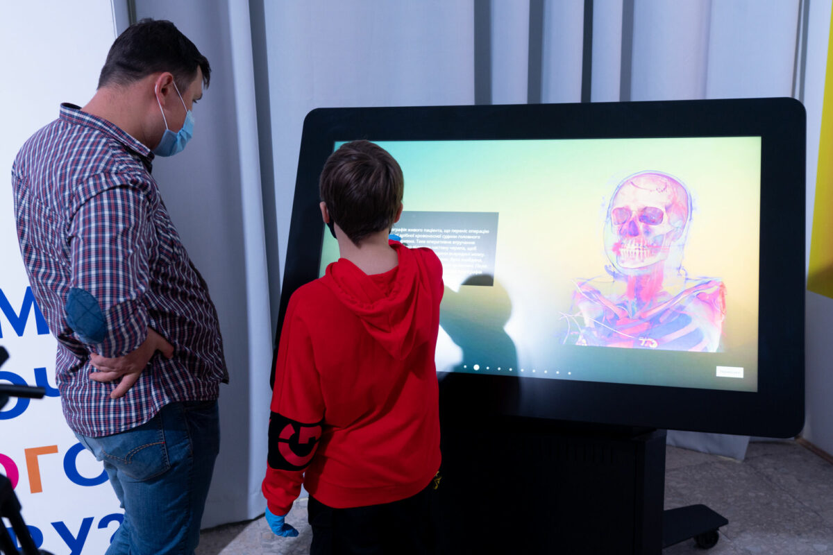 boy and man interactive with inside explorer software on touch screen